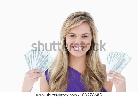 Happy blonde woman holding two fans of notes against a white background