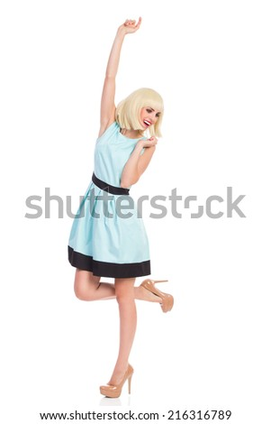 Happy blonde woman in elegance pastel blue dress, standing on one leg and raising arm. Full length studio shot isolated on white. - stock photo