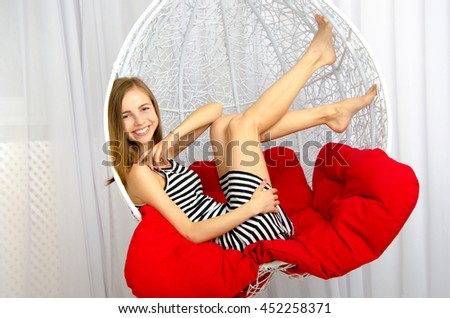 happy blonde woman lying in the beautiful chair and smiling on the camera