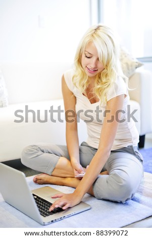 Happy blonde woman online shopping on internet at home - stock photo