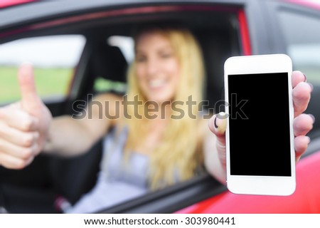 Happy blonde woman showing smartphone and showing thumb up out the window of a car. Focus on mobile phone. - stock photo