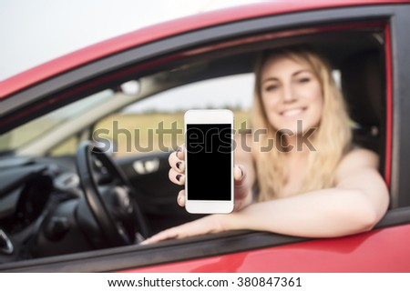 Happy blonde woman showing smartphone out the window of a car. Focus on mobile phone. - stock photo