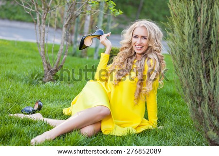 Happy blonde woman sitting outdoors at summer Field