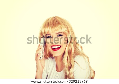 Happy blonde woman using cellphone.