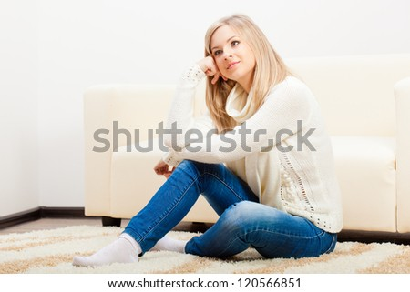 happy  blonde woman wearing sweater sitting  on carpet near sofa - stock photo
