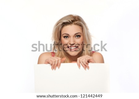 Happy blonde woman with a beautiful smile holding a blank white sign with copyspace for your text or advertisement in front of her body - stock photo