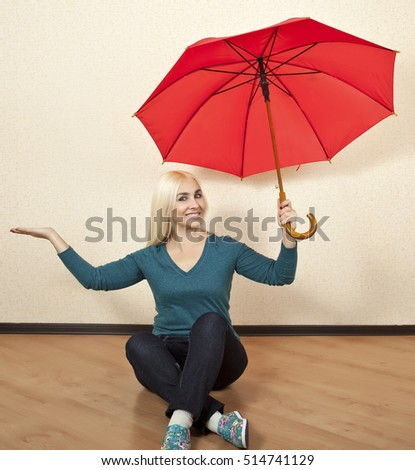 Happy blonde woman with red umbrella sitting on the floor