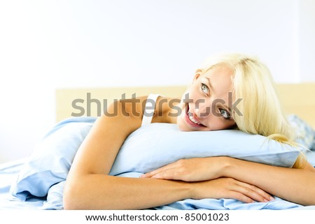 Happy blonde young woman laying in bed dreaming and smiling - stock photo
