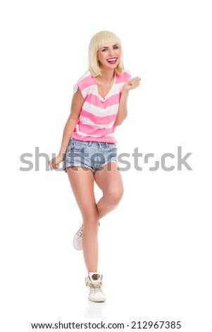 Happy blonde young woman standing on one leg. Full length studio shot isolated on white. - stock photo