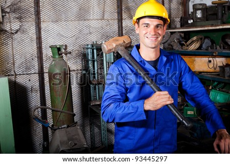 happy blue collar worker with a big hammer - stock photo