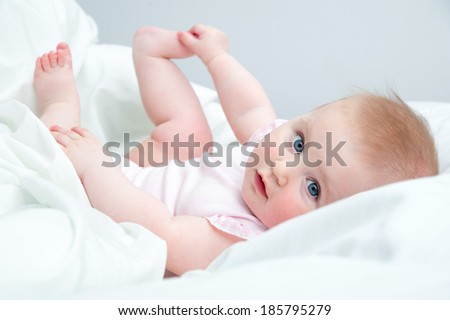 Happy blue-eyed baby playing with his feet on the bed - stock photo