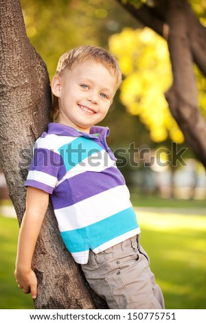 Happy blue-eyed little boy on the walk in the park hugging a tree - stock photo