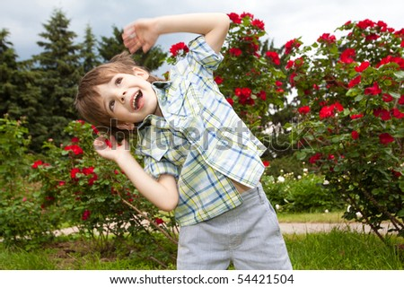 Happy boy against of rose bushes - stock photo