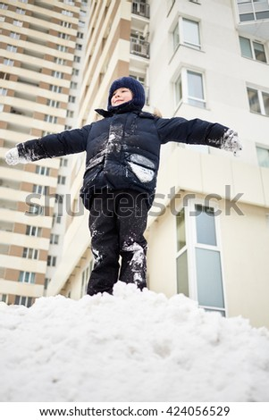 Happy boy all in snow stands on the top of snow pile in the courtyard. - stock photo