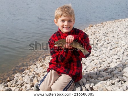 Happy boy and a Rainbow Trout fish caught fly fishing at a lake - stock photo
