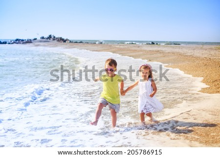 happy boy and girl running on the beach, smile