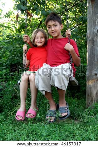 happy boy and girl sitting on swing - stock photo