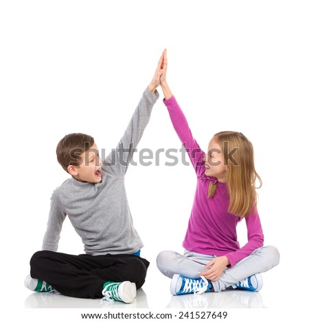 Happy boy and girl sitting on the floor with legs crossed and giving high-five to each other. Full length studio shot isolated on white. - stock photo