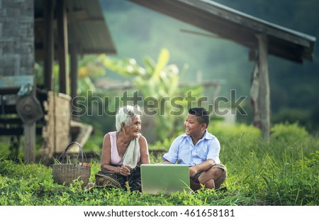 Happy boy and grandmother using a laptop outdoors