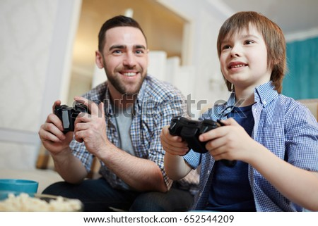 Happy boy and his father playing video games at home