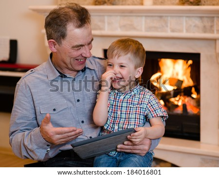 Happy boy and his grandfather using a tablet computer - stock photo