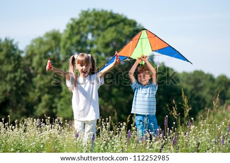 Happy boy and little girl running with bright kite on a meadow in a sunny day