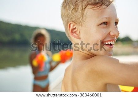 Happy boy at a lake with a squirt gun in summer - stock photo