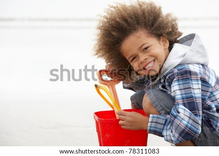 Happy boy at beach with bucket and spade - stock photo