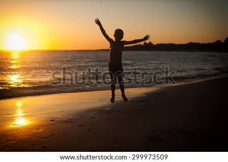 Happy boy at sunset with hands raised