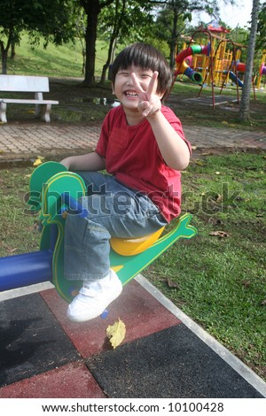 Happy boy at the playground in the park - stock photo