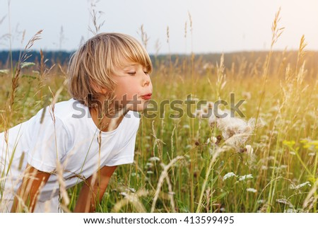 Happy boy blowing on a dandelion in the summer field . - stock photo