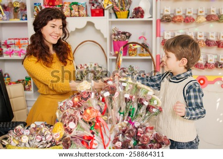Happy boy buying sweets in the store. Beautiful woman salesman gives candies to boy - stock photo
