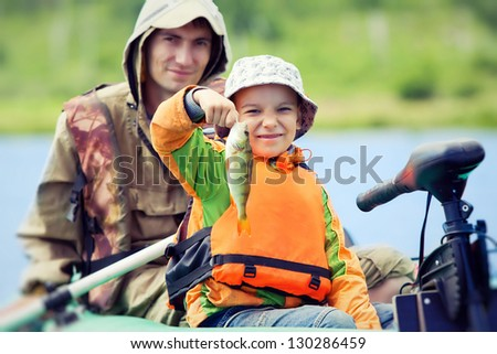 Happy boy catches his first fish - stock photo