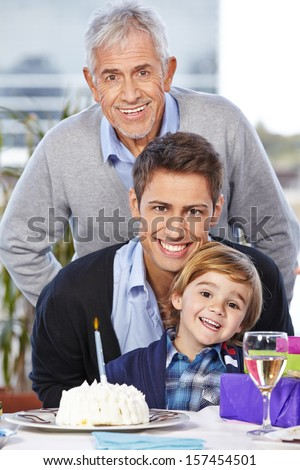 Happy boy celebrating his birthday with his father and grandfather - stock photo