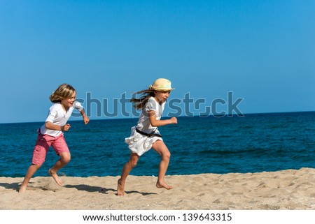 Happy boy chasing girlfriend on sunny beach. - stock photo