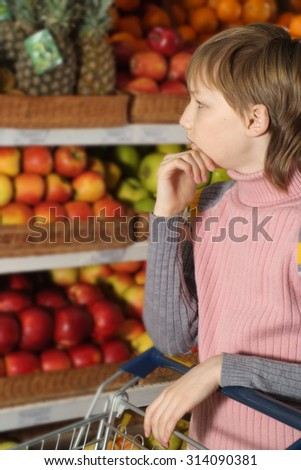 Happy boy chooses products in the store - stock photo