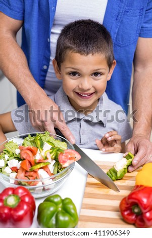 Happy boy chopping vegetables in the kitchen - stock photo