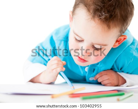 Happy boy coloring a book - isolated over a white background