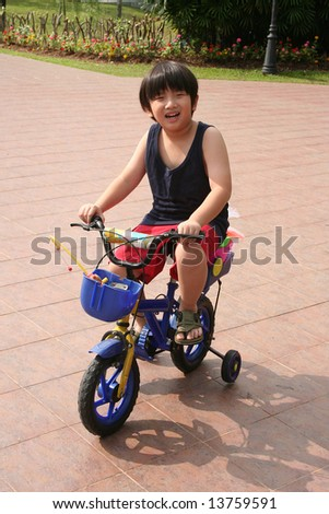 Happy boy cycling at the park in the afternoon - stock photo