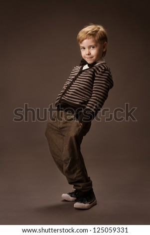 Happy Boy dancing over brown background. Vintage style. Kids fashion - stock photo