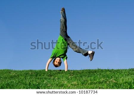 happy boy doing a cartwheel - stock photo