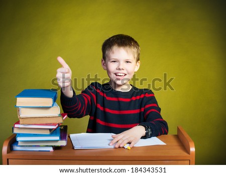 Happy boy doing homework with thumb up, books on table.