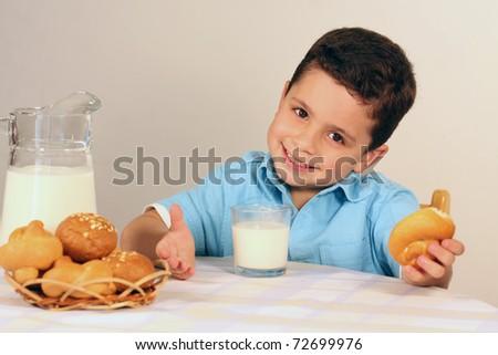 Happy boy drinking milk in the kitchen - stock photo