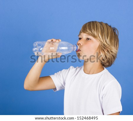 Happy boy drinks water from a bottle