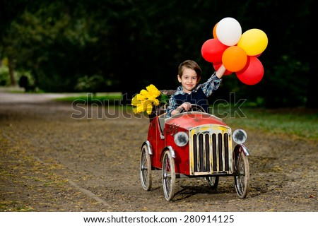 Happy boy driving old toy car with colorful balloons and yellow flowers - stock photo