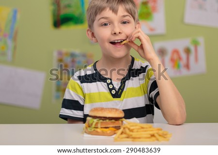 Happy boy eating unhealthy french fries for lunch - stock photo