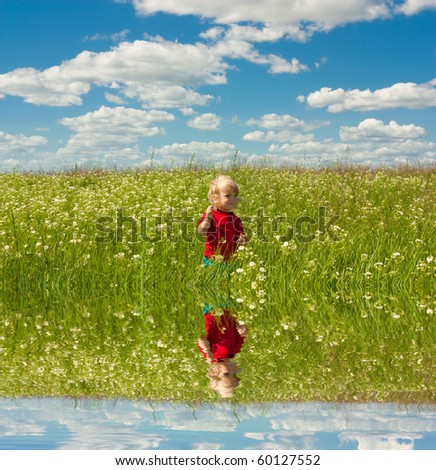 Happy boy enjoy on the meadow. Specular reflection in the water. - stock photo