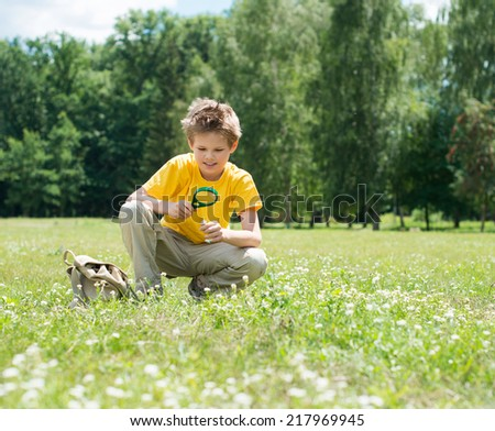 Happy boy enjoying sunny summer or autumn day in nature on green grass. Kid with magnifying glass outdoors. - stock photo