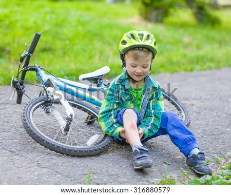 happy boy fell from the bike in a park - stock photo