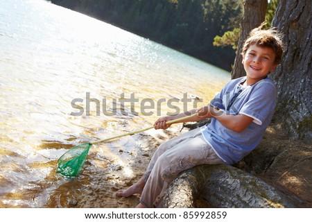 Happy boy fishing at lake - stock photo